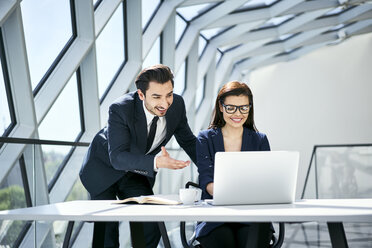 Smiling businesswoman and businessman using laptop at desk in modern office - BSZF00499