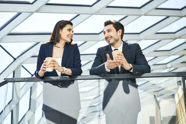 Smiling businesswoman and businessman having a coffee break in modern office - BSZF00526