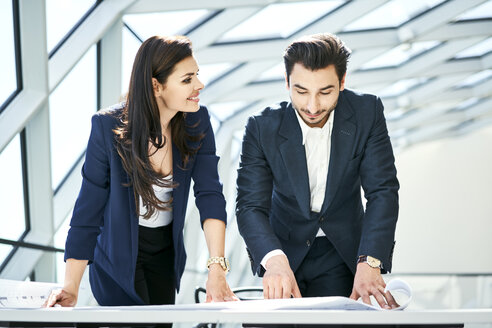 Smiling businesswoman and businessman looking at plan in office - BSZF00535