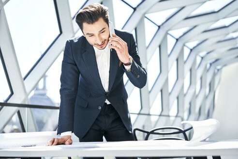 Businessman on cell phone looking at plan in office - BSZF00538