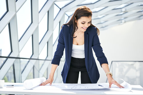 Smiling businesswoman looking at plan in office - BSZF00541