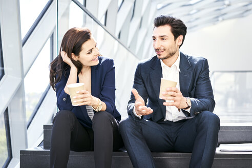 Smiling businesswoman and businessman having a coffee break in modern office - BSZF00550