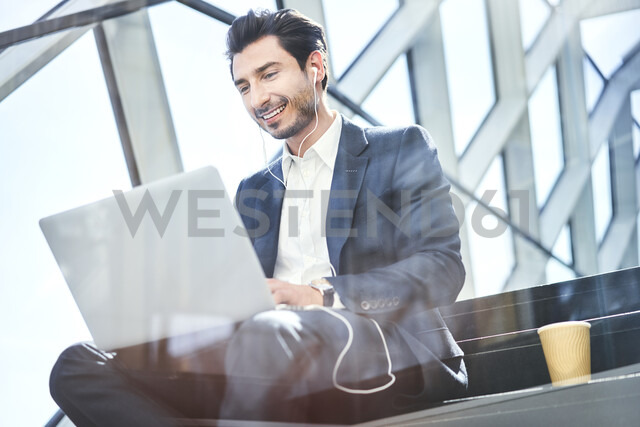 Smiling businessman sitting on stairs wearing earphones and using laptop - BSZF00556