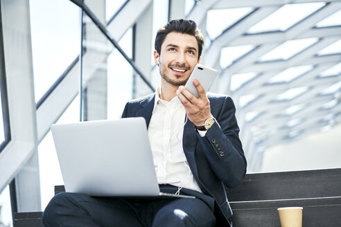 Smiling businessman sitting on stairs wearing earphones using cell phone and laptop - BSZF00559