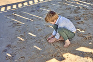 Boy playing in sand at beach - BEF00126