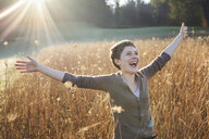 Portrait of laughing woman relaxing in nature - PNEF00641