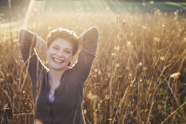 Portrait of laughing woman relaxing in nature - PNEF00644