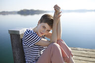 Portrait of woman sitting on jetty at lake - PNEF00647