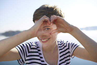 Portrait of smiling woman in front of lake shaping heart with her fingers - PNEF00653