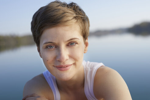 Portrait of smiling woman in front of lake - PNEF00659