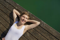 Portrait of smiling woman lying on jetty - PNEF00662