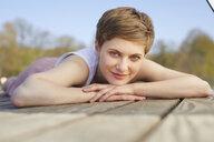 Portrait of smiling woman lying on jetty - PNEF00668