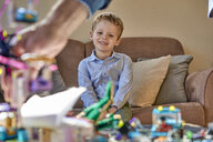 Smiling boy sitting on couch looking at toys on table - BEF00139