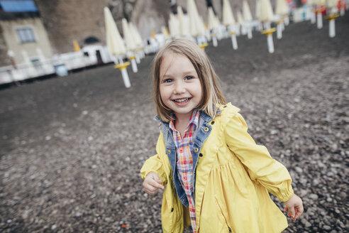Portrait of happy little girl on boardwalk on black lava beach - KMKF00252