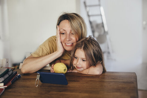 Mother and little daughter using smartphone at new home - KMKF00255