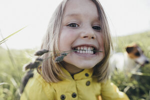 Portrait of little girl on a meadow holding blade of grass with her teeth - KMKF00261