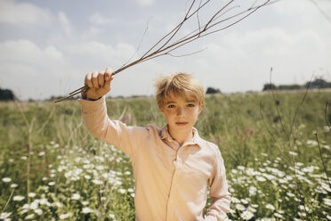 Portrait of blond boy with twigs in nature - KMKF00264