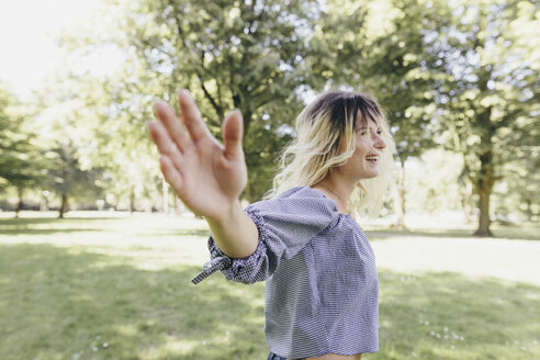 Happy young woman with outstretched arms in a park - KMKF00273