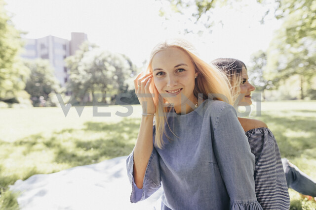Portrait of two smiling young women relaxing in a park - KMKF00276