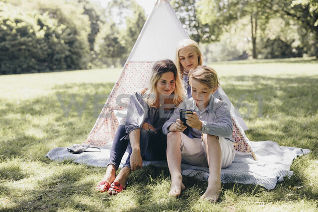 Two young women and a boy looking at cell phone next to teepee in a park - KMKF00279