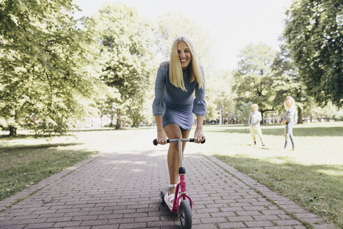 Happy young woman riding scooter in a park - KMKF00282