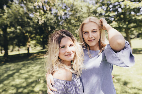 Portrait of two smiling young women embracing in a park - KMKF00285