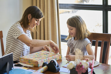 Mother and daughter packing gift at table at home - BEF00165