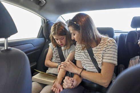Mother and daughter sitting on backseat in car reading book together - BEF00168