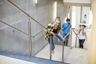 Young female student sliding down stairway handrail at higher education college - CUF22180