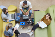 Overhead view of four male and female students brainstorming in higher education college study space - CUF22201