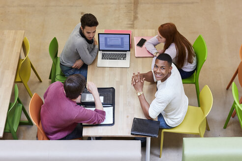 Overhead view of male and female students brainstorming in higher education college study space - CUF22204