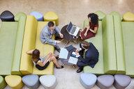 Overhead view of businessmen and businesswomen meeting on design studio sofas - CUF22246