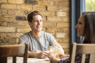 Young couple laughing and talking in bar - CUF22267