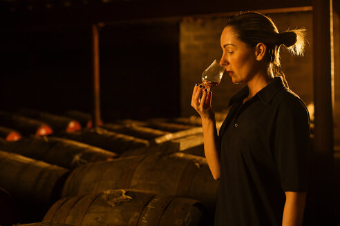 Female taster smelling whisky in glass at whisky distillery - CUF22339