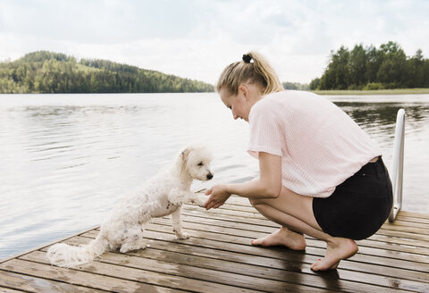 Woman holding coton de tulear dog's paw after swimming, Orivesi, Finland - CUF22372