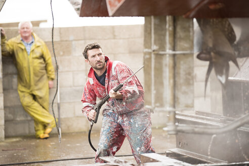 Male ship painter cleaning ship hull with pressure washer in ship painters yard - CUF22408