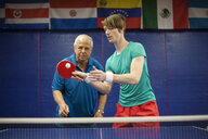 Table tennis coach watching student play - ISF07961