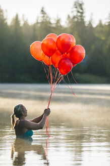 Woman in water holding bunch of red balloons - ISF07979