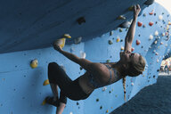 Young woman on climbing wall, Brooklyn Bridge Park, Brooklyn, New York, USA - ISF07994