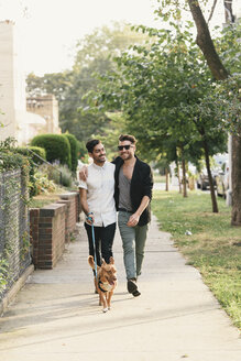 Young male couple walking dog on suburban sidewalk - ISF08012