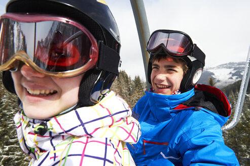 Teenage boy and girl on ski lift - ISF08102