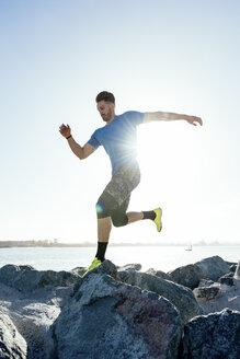 Man training, running on sunlit coast rocks, downtown San Diego, California, USA - ISF08247