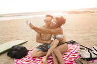 Young couple taking smartphone selfie on Rockaway Beach, New York State, USA - ISF08361