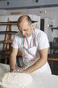 Baker in bakery, making bread - ISF08370