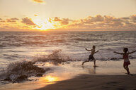 Girl and brother running on beach at sunrise, Blowing Rocks Preserve, Jupiter Island, Florida, USA - ISF08424