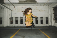 Young woman jumping mid air in indoor parking lot - ISF08448