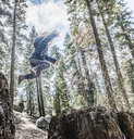 Young boy jumping in forest, mid air, Sequoia National Park, California, USA - ISF08598