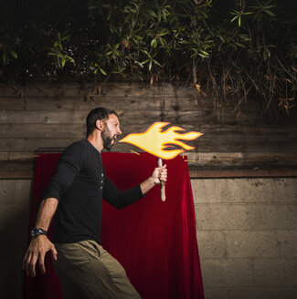 Man holding cardboard cut-out of flames pretending to breathe fire - ISF08610
