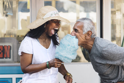 Senior couple eating cotton candy, laughing, Long Beach, California, USA - ISF08733