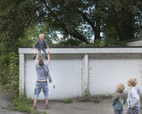 Boy jumping from garage into father's open arms - CUF22749